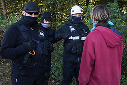 Aylesbury Vale, UK. 1st October, 2020. National Eviction Team bailiffs working on behalf of HS2 Ltd form a line in front of an anti-HS2 activist during evictions from a wildlife protection camp in ancient woodland at Jones' Hill Wood. Around 40 environmental activists and local residents, some of whom living in makeshift tree houses about 60 feet above the ground, were present during evictions at Jones' Hill Wood which had served as one of several protest camps set up along the route of the £106bn HS2 high-speed rail link in order to resist the controversial infrastructure project.