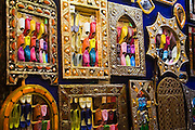 Colorful Moroccan leather oriental slippers (babouches) are reflected in ornate metal mirrors in a shop stall at a market along the streets of the Marrakech medina, Morocco.