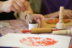 Close up of the hands of  day service users with learning disability mixing paint at an arts and crafts session,