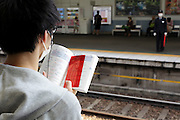 student studying while waiting for train Japan