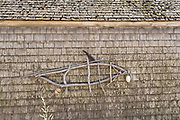 A stick sculpture of a fish on a boat house in the quaint fishing harbor of Port Clyde, Maine.