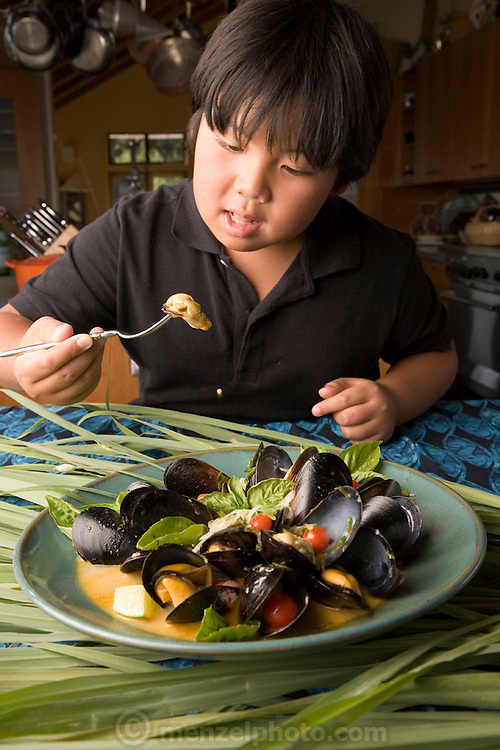 Kousuke Tominaga eats fresh mussels with lemon grass and coconut milk prepared by chef Cindy Pawlcyn for her Go Fish restaurant in the Napa Valley, California. (From the book What I Eat: Around the World in 80 Diets.)  MODEL RELEASED.