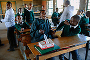 Boys react to the condom filled with air on their desk at Mahobong Secondary School. To ensure a sufficient condom supply and to halt the AIDS epidemic by 2015, the level of funding for condom procurement and distribution needs to triple.