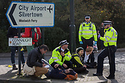 An environmental activist is arrested while protesting about Climate Change during the occupation of City Airport Londons Business Travel hub in east London, the fourth day of a two-week prolonged worldwide protest by members of Extinction Rebellion, on 10th October 2019, in London, England.