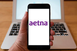 Using iPhone smartphone to display logo of Aetna; an American managed health care company
