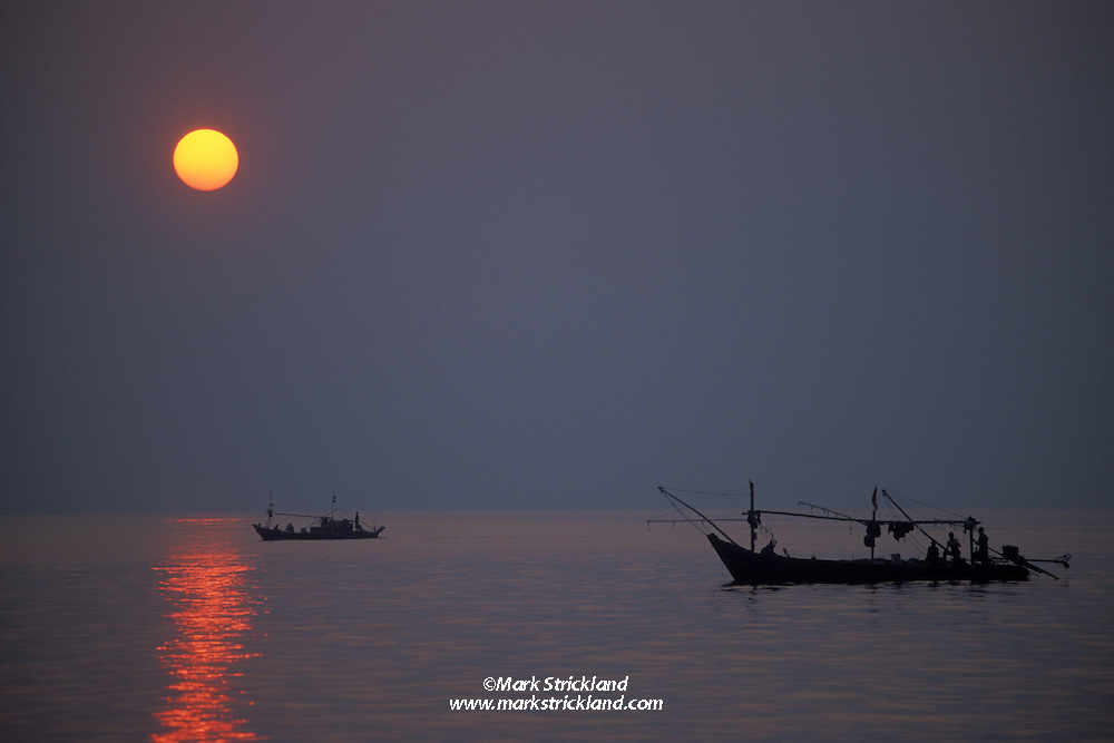 Blessed with good weather and calm seas, a pair of local boats prepare for the evening's fishing. Mergui Archipelago, Myanmar/Burma, Andaman Sea