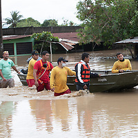 Men wade up to their waist in a flooded area after hurricanes Eta and Iota, near La Lima, Cortes, Honduras.