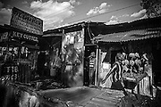 """View on Mugumoini's main road Kitengela Street of the front street entrance to the 24-hour licensed bar """"Mark 1"""" off Mugumoini's main road Kitengela Street on a normal day. Standing in the doorway is Winnie, 24, a prostitute who was raped one night on her way back from a pub just outside the Mugumoini Village area. <br /> This image is from a series focusing on and around the rape and the women victims that occur every half a day in Mugumoini Village in Nairobi's Southlands, a slum home to 20,000 people in abject poverty with little or no income, with the aim of creating exposure and empowerment for change. ©GGoodwin"""