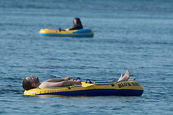© Licensed to London News Pictures. 12/05/2016. Aberystwyth, Wales, UK. A man at the seaside in Aberystwyth enjoys lying in an inflatable dingy.  The temperatures are set to fall over the coming days, with bright but colder conditions prevailing over the country .  Photo credit: Keith Morris/LNP