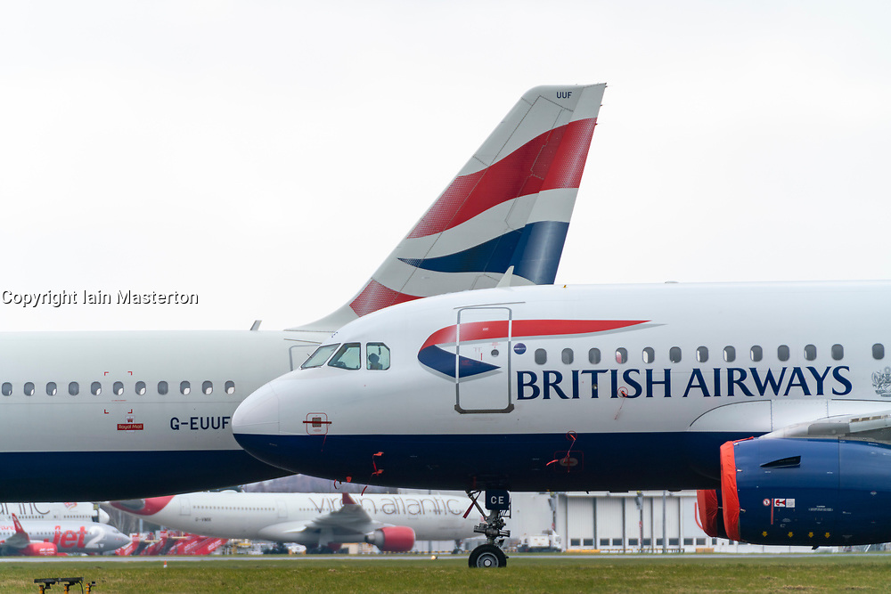 Glasgow, Scotland, UK. 25 March, 2020. Day two of the Government enforced lockdown in the UK. All shops and restaurants and most workplaces remain closed. Cities are very quiet with vast majority of population staying indoors. Pictured; British Airways passenger aircraft remain grounded and parked at Glasgow Airport. Iain Masterton/Alamy Live News