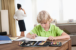 Boy studying while mother has business call, Bavaria, Germany
