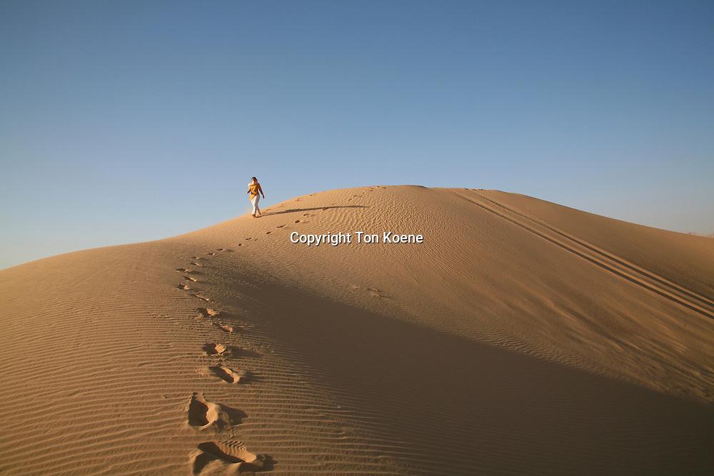 A tourist walking in the desert in Wadi Rum