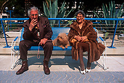 A typical elderly 1990s French couple from the Cote d'Azur sit on a bench of their seafront with their pet poodle, on 10th May 1996, in Juan-les-Pins, France. (Photo by Richard Baker / In Pictures via Getty Images)