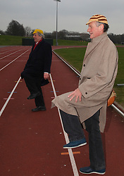 """© Licensed to London News Pictures. 03/03/2012. London, England. L-R: Terry Jones and Michael Palin doing warming up exercises. Terry Jones and Michael Palin of Monty Pythons fame today, Saturday 3 March, staged a public """"Hopathon"""" to mark the DVD release of Ripping Yarns The Complete Series, and as an homage to the episode entitled Tomkinsons School Days at the Athletics Track in  Hampstead Heath, London. Photo credit: Bettina Strenske/LNP"""