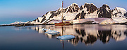 Expedition yacht Pelagic Australis moored in bay near Pleneau and Hoovgard Islands - alpenglow reflection panorama of peaks on Booth Island behind - Antarctic Peninsula