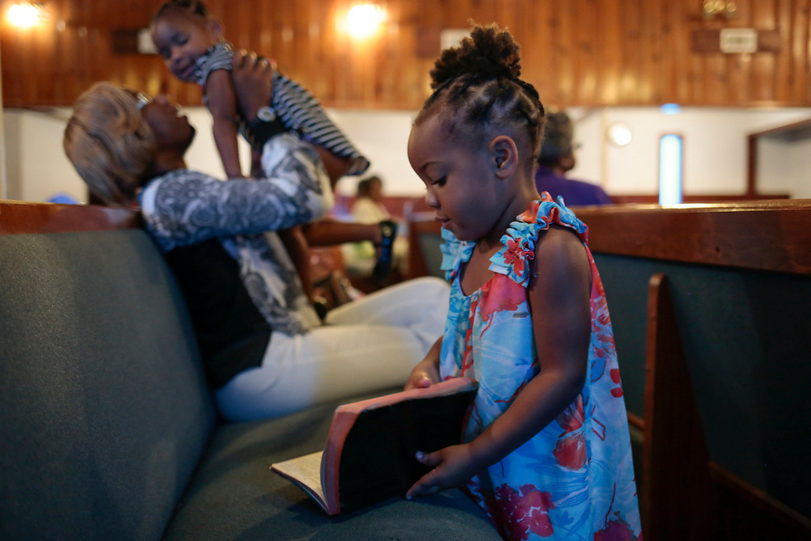 """Paris Thomas, 3, thumbs through the Bible as her mother, Coby Cochran, entertains her sister Elizabeth Thomas, 2, during the Sunday service at True Vine Missionary Baptist Church in the aftermath of tropical storm Harvey in Houston, Texas, U.S. September 10, 2017. The family lost all of their belongings in the flood and are living at a hotel with the assistance of FEMA. """"I'm a single mom and it's hard losing everything, but God is going to take care of us no matter what. Just live and love,"""" said Cochran."""