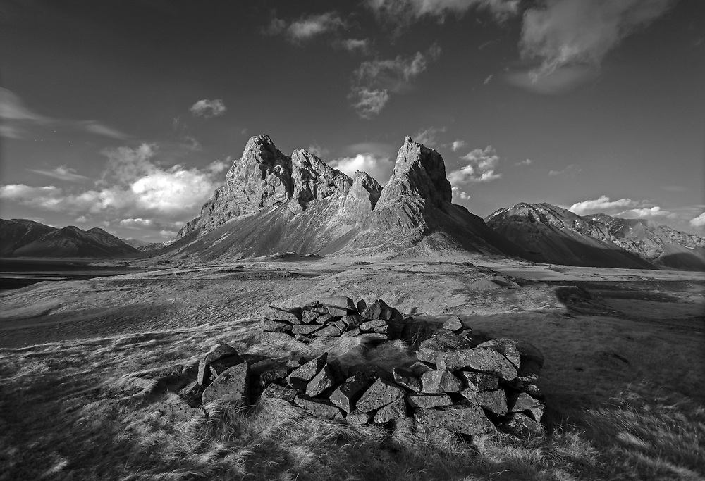 Photographed in Infrared - Ancient rocks form a circle next to a mountain range located near Reydhara, Iceland. Photo/Andrew Shurtleff Photography, LLC