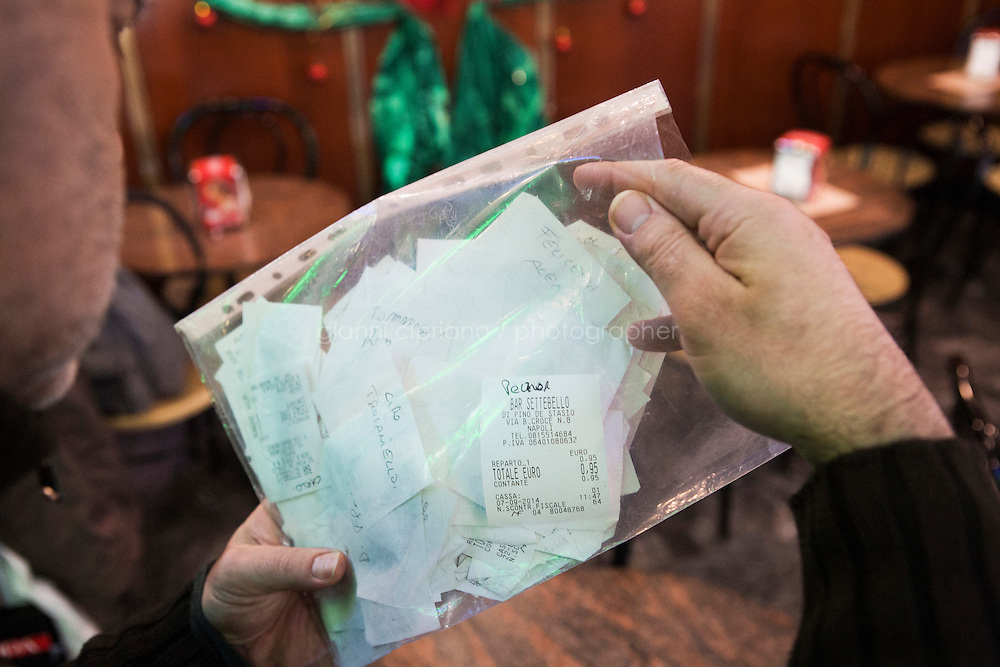 NAPLES, ITALY - 12 DECEMBER 2014: Pino De Stasio, owner of cafè Bar Settebello, shows the receipts of suspended coffees in his cafè in Naples, Italy, on December 12th 2014.<br /> <br /> A caffè sospeso,or suspended coffee, is a cup of coffee paid for in advance as an anonymous act of charity. The tradition began in the working-class cafés of Naples, where someone would order a sospeso, paying the price of two coffees but receiving and consuming only one. A poor person enquiring later whether there was a sospeso available would then be served a coffee for free.