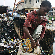 A young boy collects electronic scrap in the rain in Alaba International Market, Lagos, Nigeria.