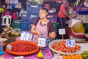 "03 OCTOBER 2012 - BANGKOK, THAILAND:  A woman sells chillies and tomatoes in Khlong Toey Market. Khlong Toey (also called Khlong Toei) Market is one of the largest ""wet markets"" in Thailand. Thousands of people shop in the sprawling market for fresh fruits and vegetables as well meat, fish and poultry every day.       PHOTO BY JACK KURTZ"