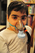 Health - young girl of 8 suffers from Asthma oxygen humidifier inhaler helps her breath - Model Release available