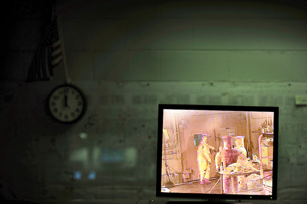 AIKEN, S.C. - NOVEMBER, 20 2013: Dressed in contamination suits, three workers are watched by a crane specialist on a video monitor in the control room of the Defense Waste Processing Facility at the Savannah River Site near Aiken, S.C. The control room remotely operates a large crane and tools needed during the vitrification process. Vitrification seals processed radioactive waste in glass for storage.  CREDIT: Stephen Morton for The New York Times