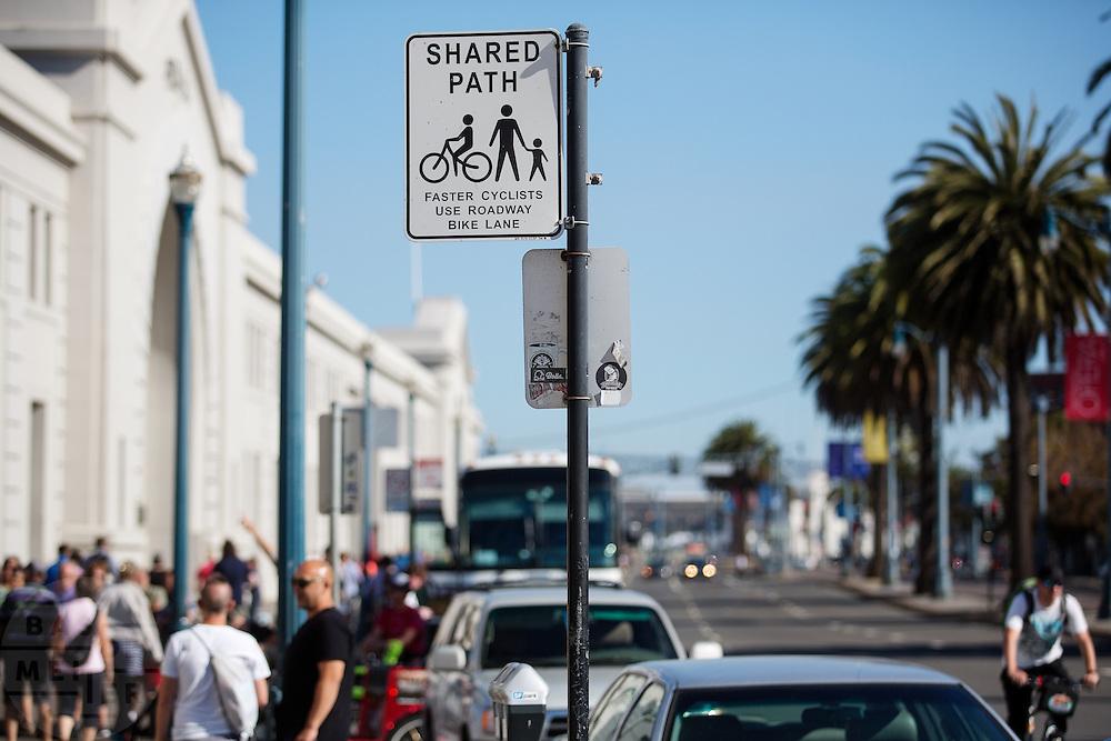 Een bord geeft aan dat fietsers en voetgangers de weg moeten delen aan de boulevard in San Francisco. De Amerikaanse stad San Francisco aan de westkust is een van de grootste steden in Amerika en kenmerkt zich door de steile heuvels in de stad. Ondanks de heuvels wordt er steeds meer gefietst in de stad.<br /> <br /> A sign indicates that cyclists and pedestrians have to share the path near the boulevard in San Francisco. The US city of San Francisco on the west coast is one of the largest cities in America and is characterized by the steep hills in the city. Despite the hills more and more people cycle.