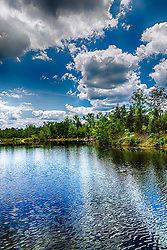 Puffy Clouds and Deep Blues Surround The Vibrant Green Foliage at Klondike Park Lake in Saint Charles County, Missouri