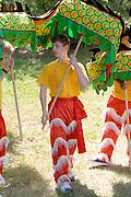 Colorful legs of the festival dance team carry dragon to ceremony. Dragon Festival Lake Phalen Park St Paul Minnesota USA