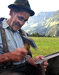"""THEMENBILD - Bergbauern in den Hohen Tauern. Mähen mit der Sense. Die steilsten Hänge am Innermarcherhof in Virgen werden von Altbauer Georg Steiner, vlg. """"Marcha Jörgl"""" und seinem Schwiegersohn Markus nach wie vor von Hand mit der Sense gemäht, Traditionell wie es seit Jahrhunderten auch ihre Vorfahren taten. Damit die Sense einen sauberen glatten Schitt erzeugt muß sie regelmässig gedengelt werden. Der Einsatz von Maschinen ist aufgrund der Steilheit der Hänge nicht möglich. Hier im Bild der Jörgl beim Dengln. Fotografiert am 04.07.2011. EXPA Pictures © 2011, PhotoCredit: EXPA/ Johann Groder"""