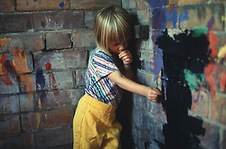 Young child standing in corner of school playground; sucking thumb and looking upset,
