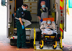 Glasgow, Scotland, UK. 15 April 2020. Elderly patient is unloaded from ambulance by staff wearing PPE at A&E department at Glasgow Royal Infirmary. Iain Masterton/Alamy Live News