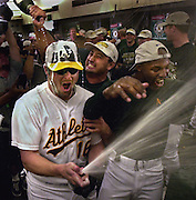 Jason Giambi sprays champagne in the lockeroom as Gill Heredia pours on him. To the right getting hit by spray is Bo Porter. Picture taken 10/1/00.