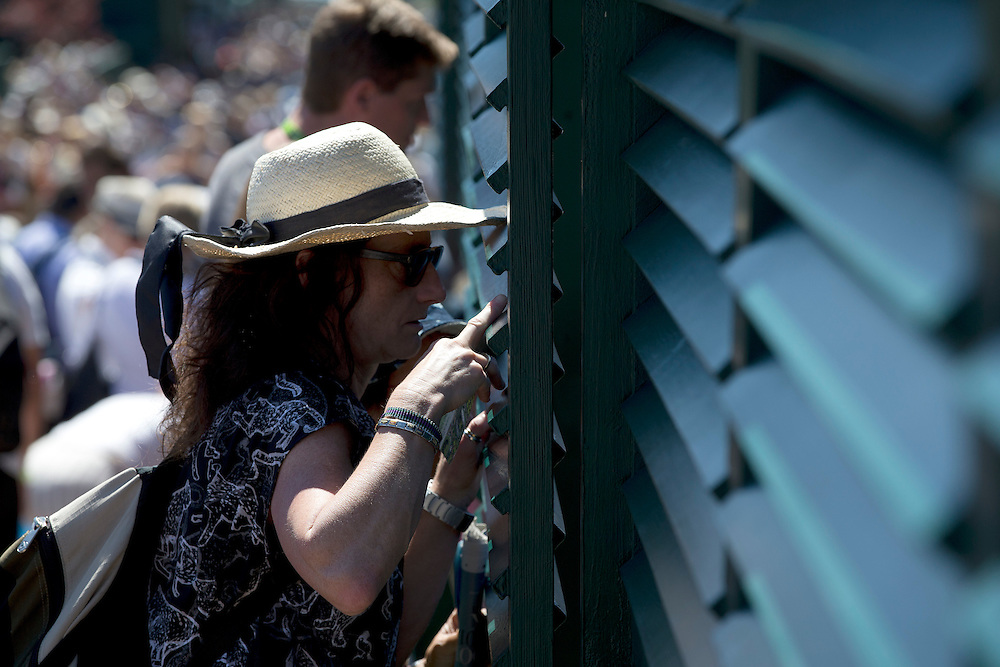 A tennis fan tries to view a match looking through the slats of the court surround<br /> <br /> Photographer Stephen White/CameraSport<br /> <br /> Tennis - Wimbledon Lawn Tennis Championships - Day 2 - Tuesday 30th June 2014 -  All England Lawn Tennis and Croquet Club - Wimbledon - London - England<br /> <br /> © CameraSport - 43 Linden Ave. Countesthorpe. Leicester. England. LE8 5PG - Tel: +44 (0) 116 277 4147 - admin@camerasport.com - www.camerasport.com.