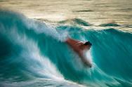 Boogie boarder catches a wave on the Kona Coast at  La'Aloa Magic Sands Beach Park, Kailua-Kona, North Kona District, Big Island, Hawaii