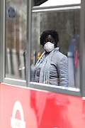 A woman wearing a face protective mask is seen reflected on a red bus nearby London Bridge station on Wednesday, April 8, 2020. At least 14 transport workers in London have died from COVID-19, prompting a new pilot scheme which will see passengers board buses using the middle door to reduce contact with drivers. (Photo/Vudi Xhymshiti)