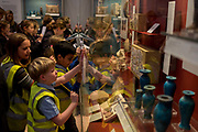 Schoolchildren wearing hi-vis jackets work on their history project in the British Museum,on 28th February 2017, in London, England.