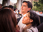 05 AUGUST 2013 - BANGKOK, THAILAND: Former Thai Prime Minister ABHISIT VEJJAJIVA stops for photos with  his supporters at a Thai Democrats' event in Bangkok Monday. Abhisit spoke at a gathering of Thai Democrats in a working class neighbohood of Bangkok off of Rama VI Road. He spoke out against the Pheu Thai's amnesty efforts, which could lead to Thaksin Shinawatra returning to Thailand.     PHOTO BY JACK KURTZ