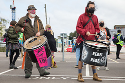 Samba drummers from Extinction Rebellion attend a protest against the expansion of Stansted Airport on 29 August 2020 in Bishop's Stortford, United Kingdom. The activists are calling on Manchester Airports Group to withdraw their appeal, for which planning permission was previously refused by Uttlesford District Council, to be able to expand Stansted Airport from a maximum of 35 million to 43 million passengers a year, as well as calling on the Government to halt all airport expansion in order to maintain its commitments under the Paris Agreement.