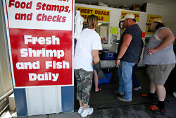 07 May 2010. Westwego, Louisiana. <br /> Westwego Fish Market. All seafood prices have risen 25% in the past 7 days alone as stocks run low thanks to closed fishing grounds affected by oil pollution. Today was the opening day of the inshore shrimp season. The season was closed before it could open thanks to BP's disastrous environmental catastrophe out in the Gulf of Mexico. Approximately 210,000 barrels of oil per day is leaking uncontrollably into the Gulf because of the explosion and collapse of the Deepwater Horizon drilling platform 46 miles out to sea. The closure of fishing grounds both east and west of the Mississippi river outflow is crippling thousands of local fishermen and all affiliated businesses and families who rely on the seafood industry. None of the shrimp or other seafood offered at the market are fresh catch from today. Everything has been through the IQF (Instant Quick Freeze) process and is seafood caught earlier in the season and brought from storage freezers in Venice and Grand Isle. Stocks are running low. With no new catches, the market will be forced to rely on farmed shrimp shipped in from Texas and Georgia. Local traders refuse to stock Chinese import fish raised with growth hormones, pesticides, fungicides and other contaminants widely found in Chinese farm raised seafood. Many fear losing their jobs and everything they own as a result of BP's Gulf Coast environmental disaster.<br /> Photo credit; Charlie Varley/varleypix.com