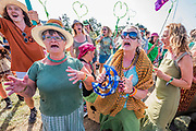 Singing in the centre of the sign - Reaching the Sacred stones a giant human version of their hour glass logo is created - The Extinction Rebellion protest march around the site, led by their Iconic pink boat, Tell the Truth - The 2019 Glastonbury Festival, Worthy Farm. Glastonbury, 27 June 2019