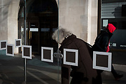 Londoners and squares on the glass screens at a bus stop in Kingston, on 7th November 2019, in London, England.