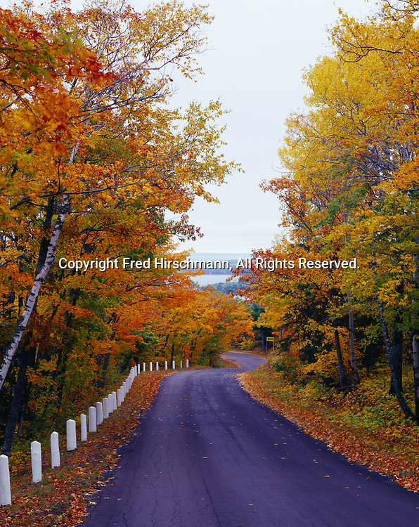 Brockway Mountain Drive winding through beautiful autumn foliage as the road descends to Copper Harbor, Keweenaw Peninsula, Upper Peninsula of Michigan.