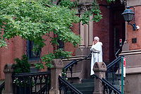 A priest having a smoke outside the priory of the church of St. Vincent Ferrer on Lexington Avenue and 65th Street.