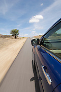 A car driving at speed on a road in an arid landscape in Namibia