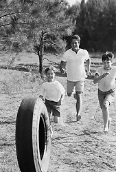 Man and two boys chasing a tire in the country