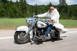 Rich Robbins (Buddha) riding in his trademark white Yeti coat on the Cycle Source ride down Vanocker Canyon back from Nemo to the Iron Horst Saloon during the Sturgis Black Hills Motorcycle Rally. SD, USA. Wednesday, August 7, 2019. Photography ©2019 Michael Lichter.