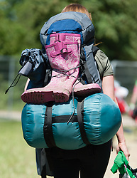 © Licensed to London News Pictures. 11/06/2015. Newport, UK.  Wellies being carried by a festival goers as she arrives at the Isle of Wight Festival 2015 carrying their tents and belongings just after being allowed onto the campsite at midday. The weather is warm and sunny but rain is expected tomorrow.This years festival include headline artists the Prodigy, Blur and Fleetwood Mac.  Photo credit : Richard Isaac/LNP