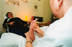 Reflexologist working with patient at a drugs clinic; W,Yorkshire