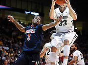 SHOT 1/21/12 5:41:11 PM - Colorado's Austin Dufault #33 grabs a rebound in front of Arizona's Kevin Parrom #3 during their PAC 12 regular season men's basketball game at the Coors Events Center in Boulder, Co. Colorado won the game 64-63..(Photo by Marc Piscotty / © 2012)